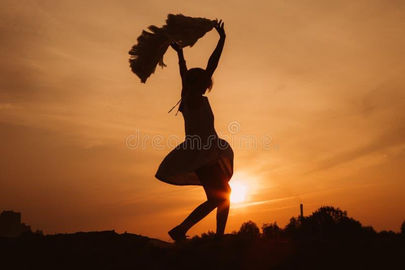 La montagne supérieure de femme se réjouit le coucher du soleil de danses photo stock