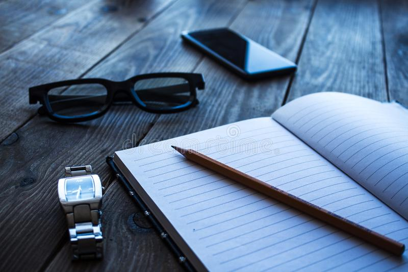 La montre de carnet et de crayon téléphonent le bacground en bois de glasseson photo libre de droits