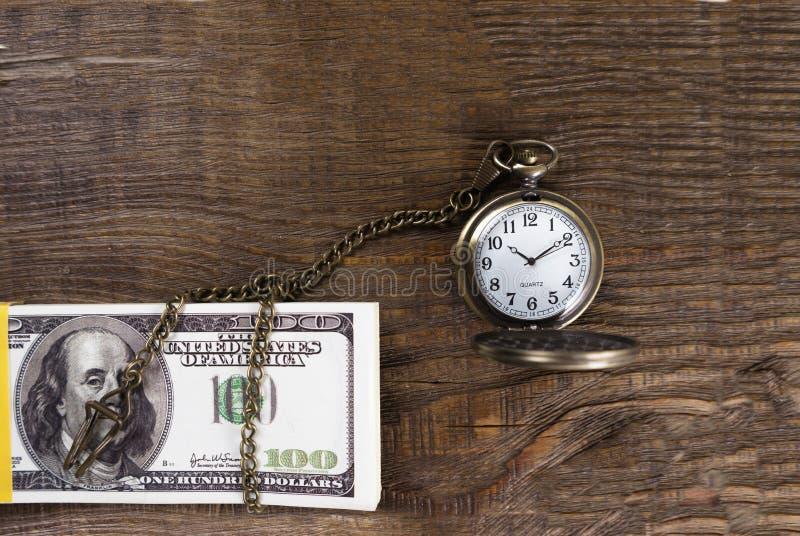 La montre de poche s'est associée à encaissent dedans l'arbre Le temps, c'est de l'argent images stock
