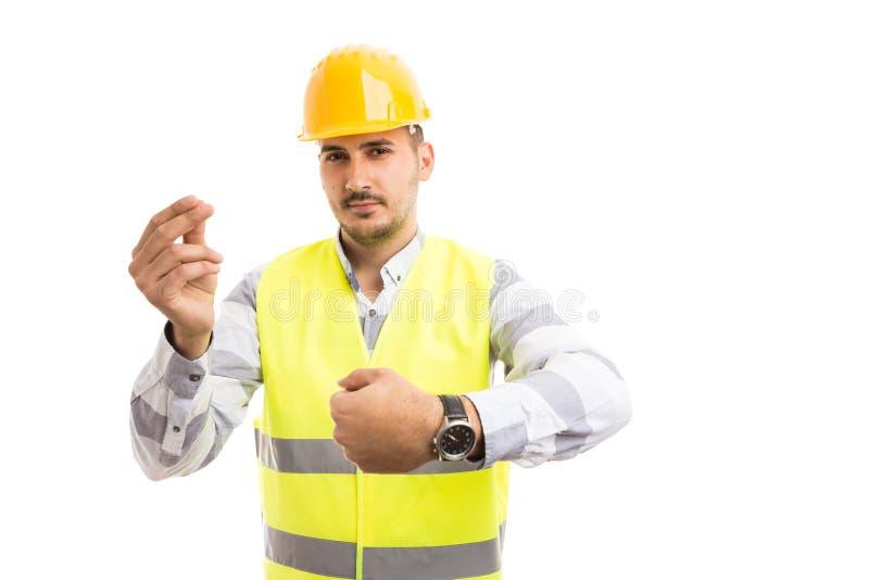 La montre et l'argent d'apparence d'ingénieur ou d'architecte font des gestes photos libres de droits