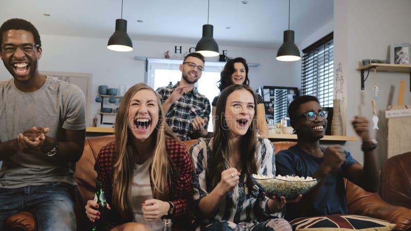 La montre interculturelle de groupe folâtre le jeu à la TV Les défenseurs passionnés célèbrent le but avec des boissons fin du mo photo stock