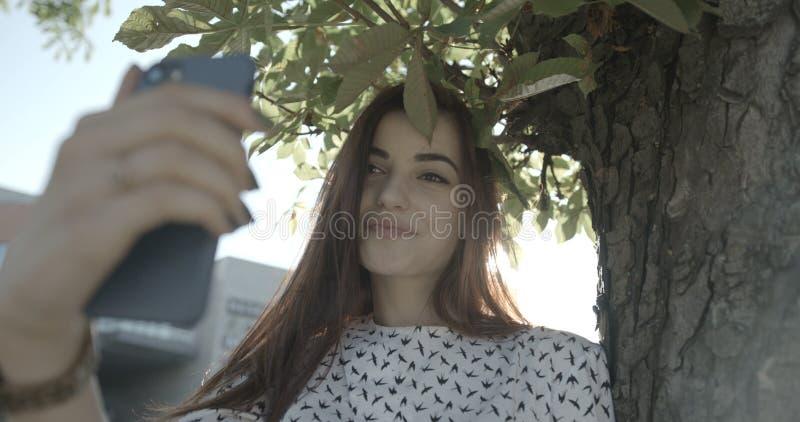 La morenita adorable es sonriente y que toma el selfie en el teléfono móvil en rayos de sol en parque cantidad 4k fotos de archivo libres de regalías