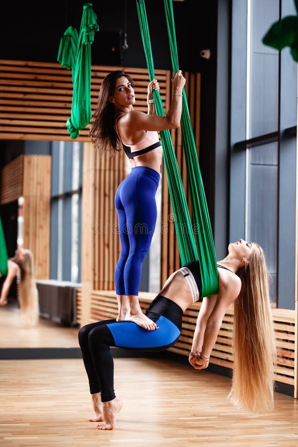 La morenita atl?tica de dos muchachas y rubios jovenes est?n haciendo aptitud en la seda a?rea verde en el gimnasio moderno fotos de archivo libres de regalías