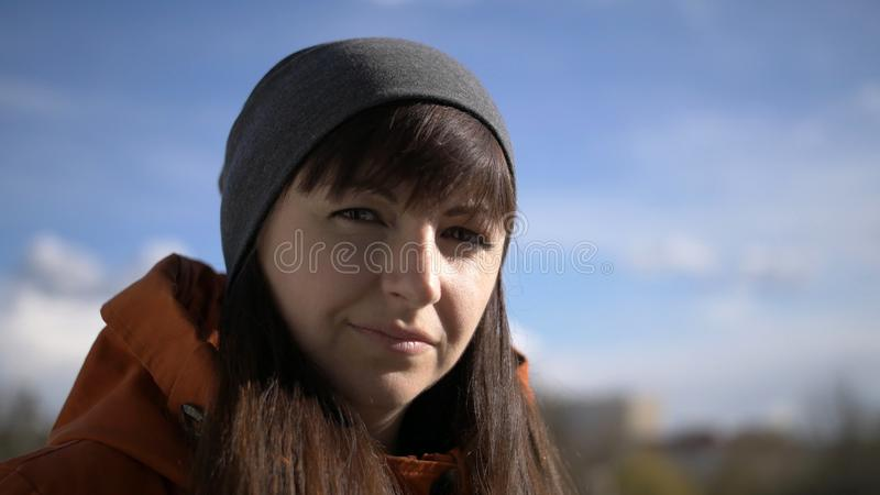 La morenita atractiva con la muchacha de las explosiones con los ojos marrones en sombrero gris y chaqueta anaranjada se está col imágenes de archivo libres de regalías