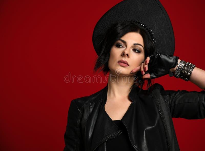 La morenita atractiva y brutal de la mujer en ropa elegante del neofolk ennegrece la chaqueta de cuero y el kokoshnik negro mira  foto de archivo libre de regalías