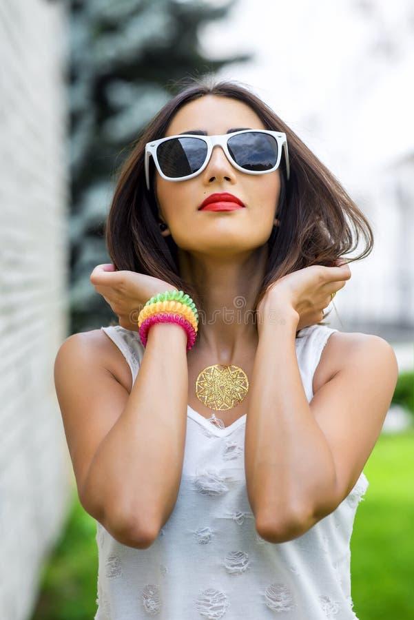 La morenita de la muchacha en verano en la blusa blanca del parque en forma de vida de la moda del fondo, trata mirada con suavid imagen de archivo