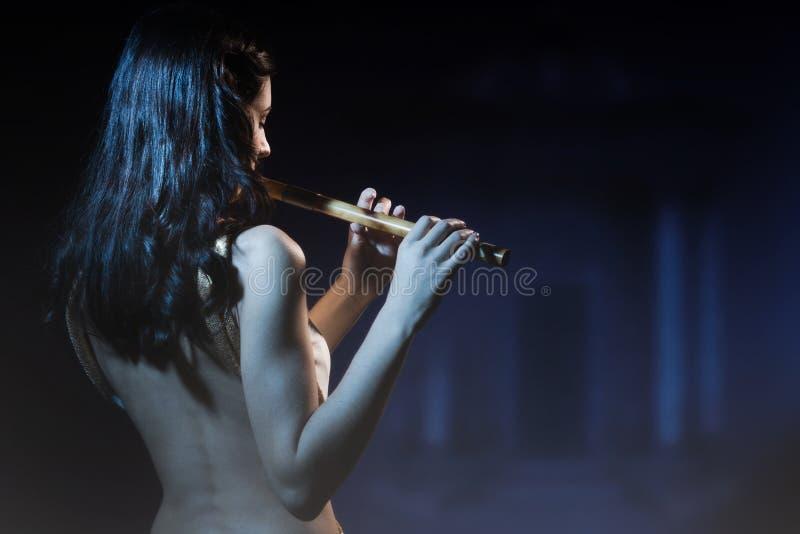 La morenita de la sensualidad toca una flauta de madera fotos de archivo
