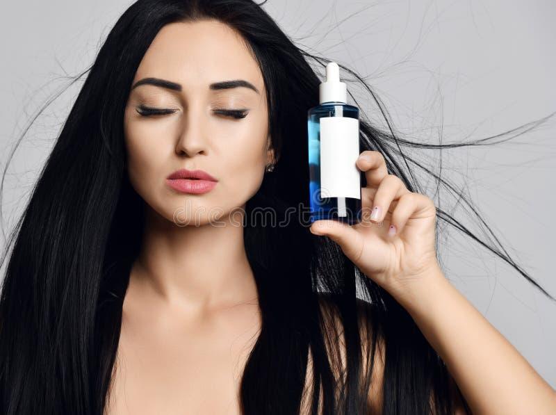 La morenita de la mujer con el pelo largo que agita en el viento y los ojos cerrados muestra una botella con el cosmético en gris fotos de archivo libres de regalías