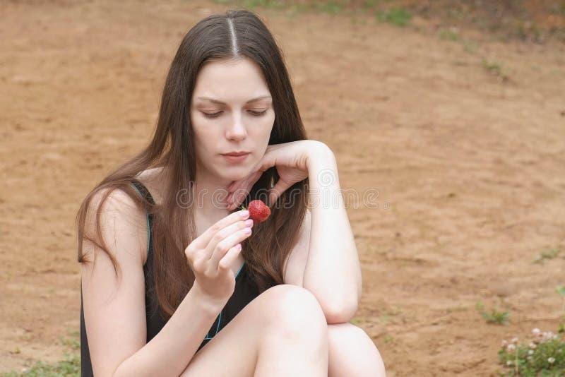 La morenita de la mujer joven come una fresa que se sienta en la playa imágenes de archivo libres de regalías