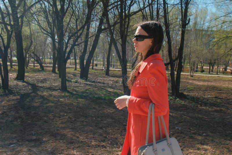 La morenita de la mujer joven en gafas de sol en capa roja camina en el parque de la primavera imagen de archivo