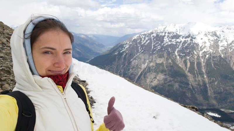 La morenita del viajero de la muchacha toma un selfie y muestra un pulgar para arriba contra las monta?as Viaje con una mochila fotos de archivo libres de regalías