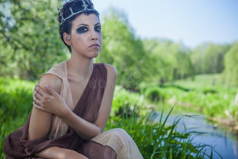 La morenita delgada en un vestido anaranjado se está colocando en la orilla de una charca del bosque foto de archivo