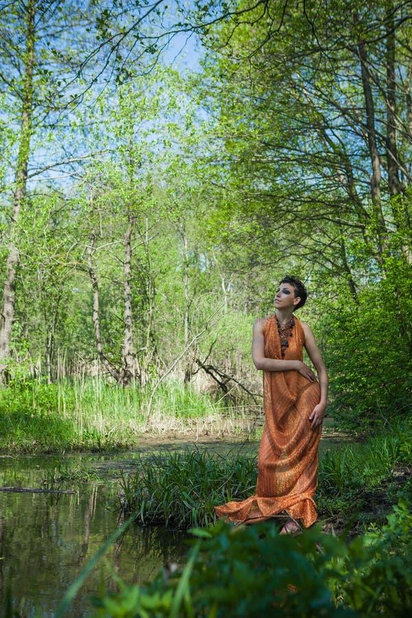 La morenita delgada en un vestido anaranjado se está colocando en la orilla de una charca del bosque fotografía de archivo