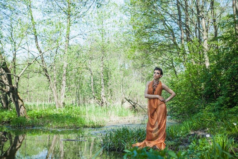 La morenita delgada en un vestido anaranjado se está colocando en la orilla de una charca del bosque fotos de archivo libres de regalías