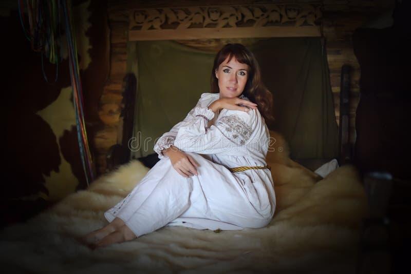 La morenita en la camisa pasada de moda de lino blanca con bordado se sienta en una cama medieval fotos de archivo libres de regalías