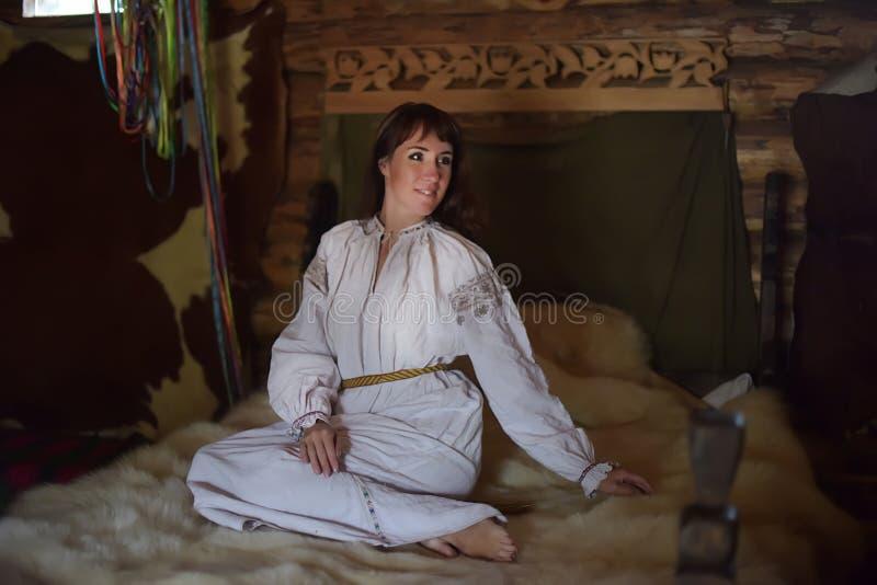 La morenita en la camisa pasada de moda de lino blanca con bordado se sienta en una cama medieval foto de archivo libre de regalías
