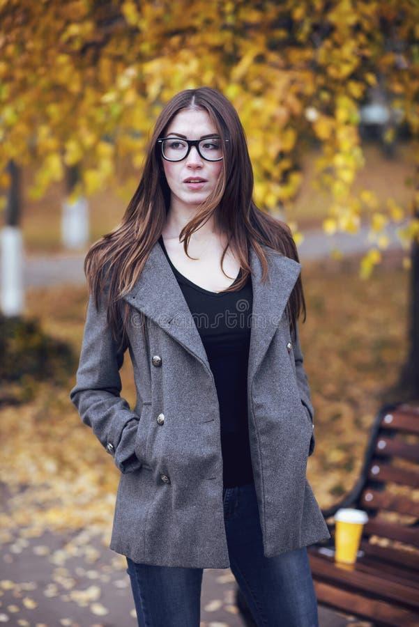 La morenita en un parque en vidrios que llevan de la capa, otoño o primavera de la muchacha, camina en la ciudad, esperando a nov foto de archivo libre de regalías