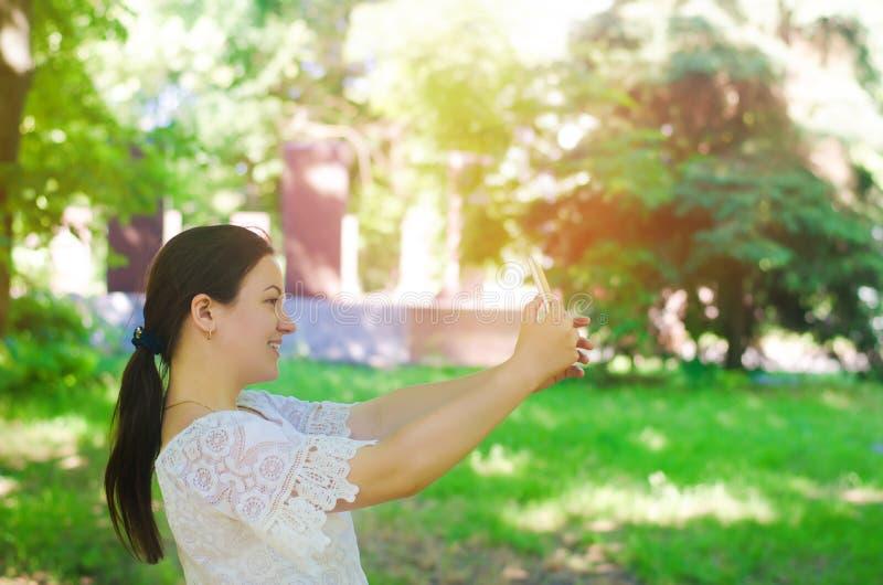 La morenita europea joven hermosa de la muchacha toma una imagen de sí misma y hace el selfie en el parque de la ciudad gente, fo foto de archivo
