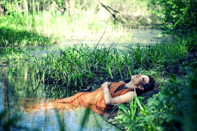 La morenita fina en un vestido anaranjado miente en una charca fotografía de archivo libre de regalías