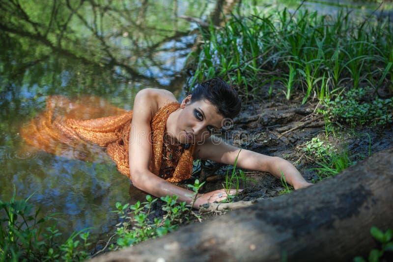 La morenita fina en un vestido anaranjado miente en una charca fotos de archivo libres de regalías