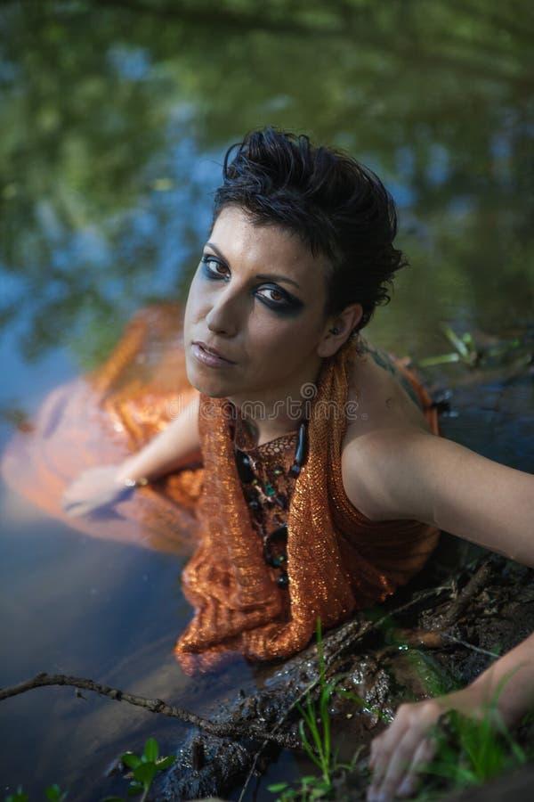 La morenita fina en un vestido anaranjado miente en una charca fotografía de archivo