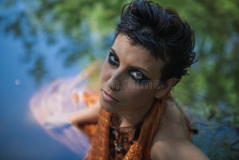 La morenita fina en un vestido anaranjado miente en una charca foto de archivo