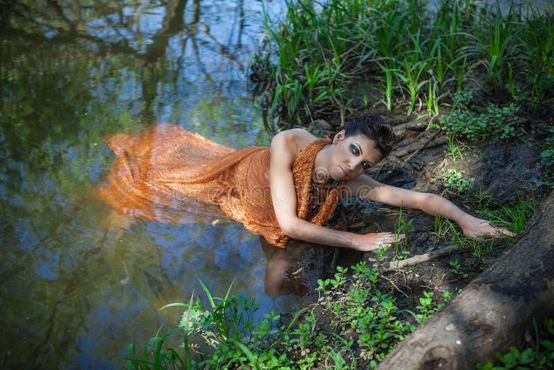 La morenita fina en un vestido anaranjado miente en una charca imagen de archivo