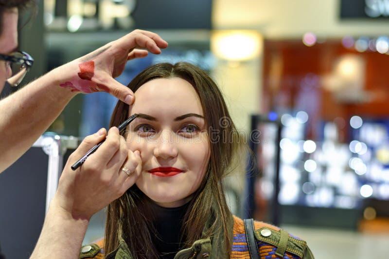 La morenita hermosa con el lápiz labial rojo está probando los sombreadores de ojos en tienda de la belleza fotos de archivo libres de regalías
