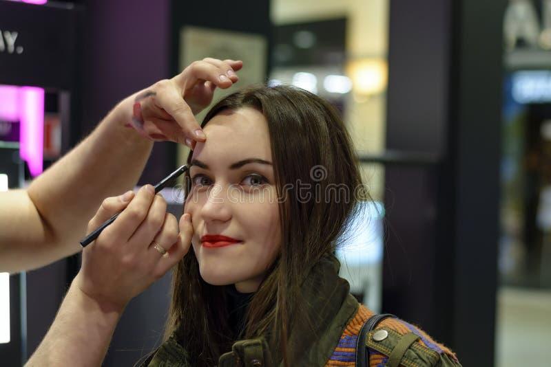 La morenita hermosa con el lápiz labial rojo está probando los sombreadores de ojos en tienda de la belleza fotografía de archivo