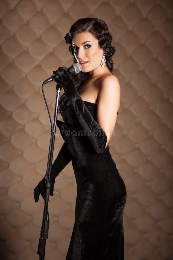 La morenita hermosa con un micrófono canta una canción en etapa foto de archivo