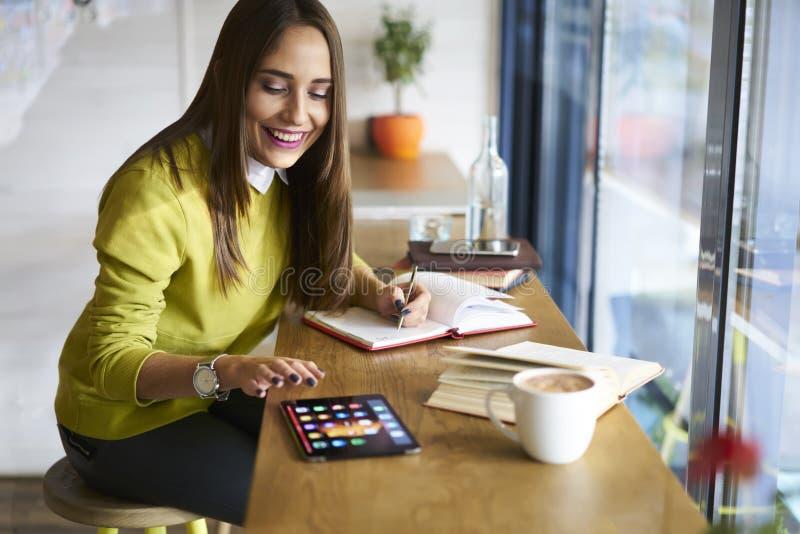 La morenita hermosa en juegos de una blusa del amarillo en panel táctil con mofa encima de la pantalla conectó con Internet inalá imagenes de archivo