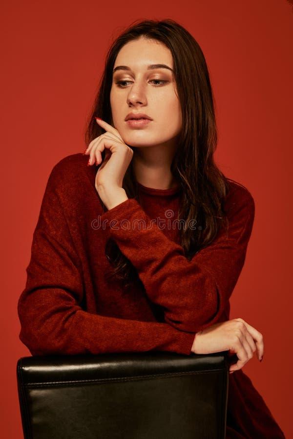 La morenita hermosa joven pensativa en vestido del boho se sienta inclinándose los brazos en la parte de atrás de una silla imagenes de archivo