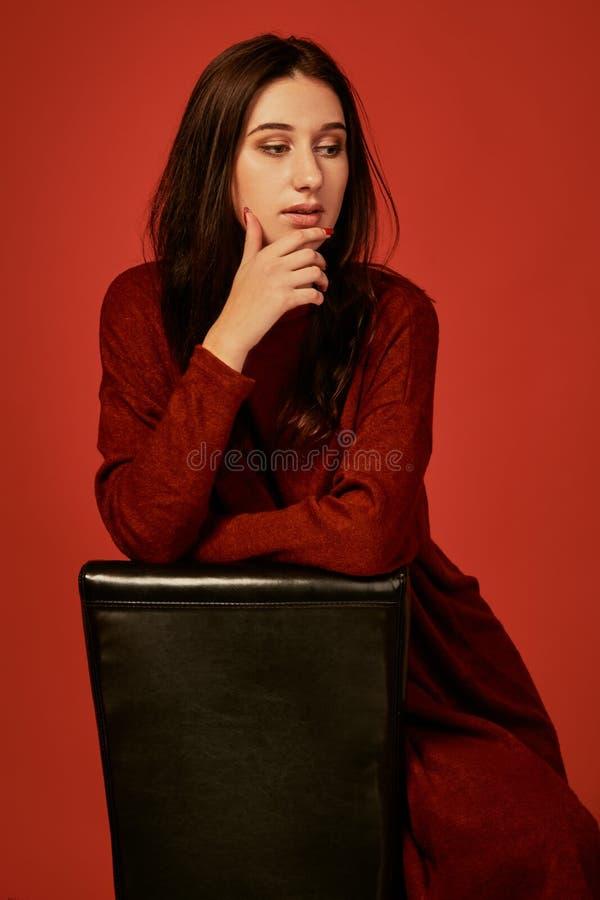 La morenita hermosa joven pensativa en vestido del boho se sienta inclinándose los brazos en la parte de atrás de una silla foto de archivo