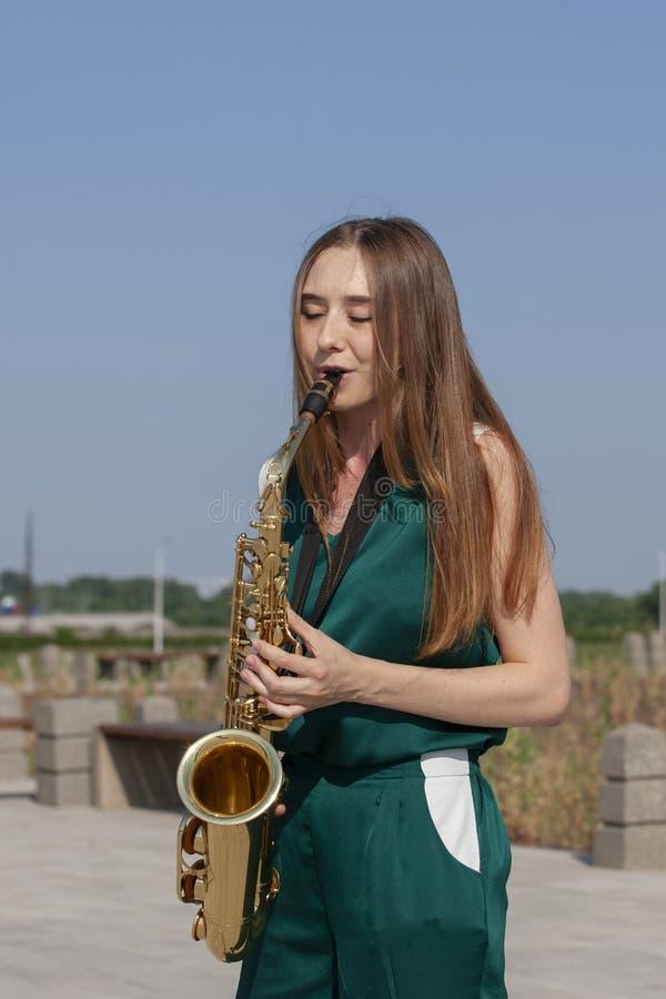 La morenita hermosa toca el saxofón en el parque imagen de archivo libre de regalías