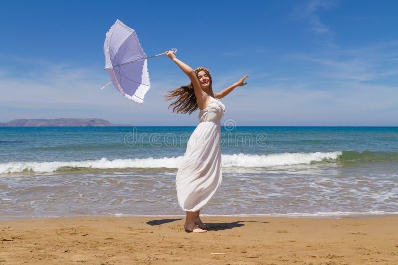 La morenita joven en el vestido débil blanco goza de imagen de archivo