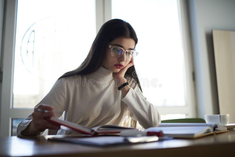 La morenita joven enganchó a la universidad que se sentaba en la tabla en biblioteca de universidad foto de archivo