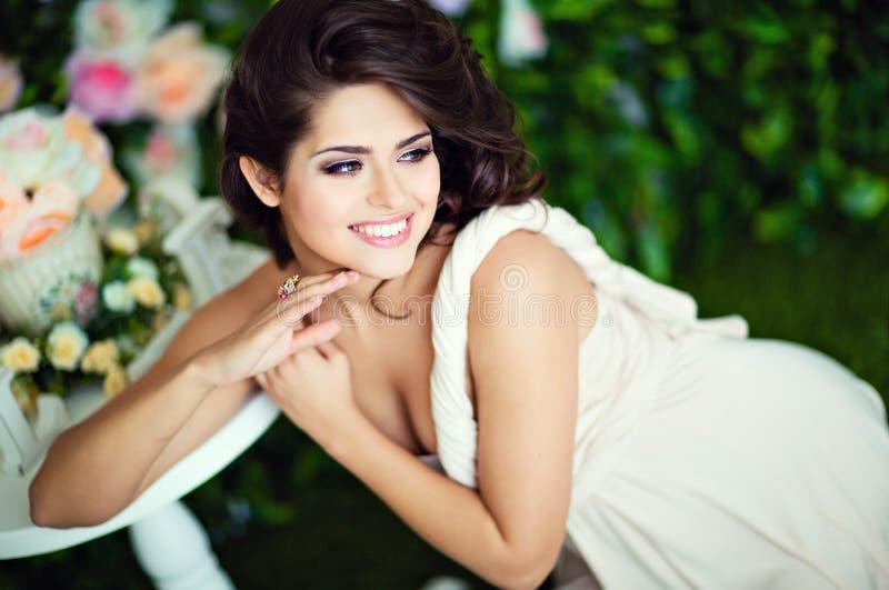 La morenita muy hermosa de la muchacha en un vestido beige ríe y mira a foto de archivo