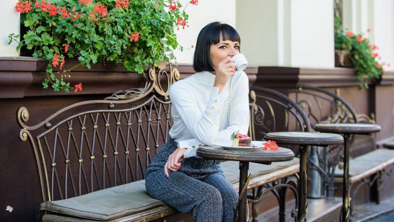 La morenita soñadora de la cara del maquillaje de la mujer come el fondo de la terraza del café de la torta Disfrute gastronómico fotos de archivo libres de regalías