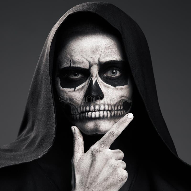 La mort effrayante considère soutenir le sien tête-bras photos stock
