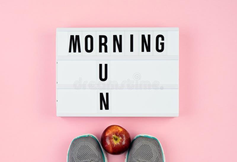 La motivazione cita sulla scatola leggera, sulla mela e sulle scarpe di sport sul rosa fotografia stock libera da diritti