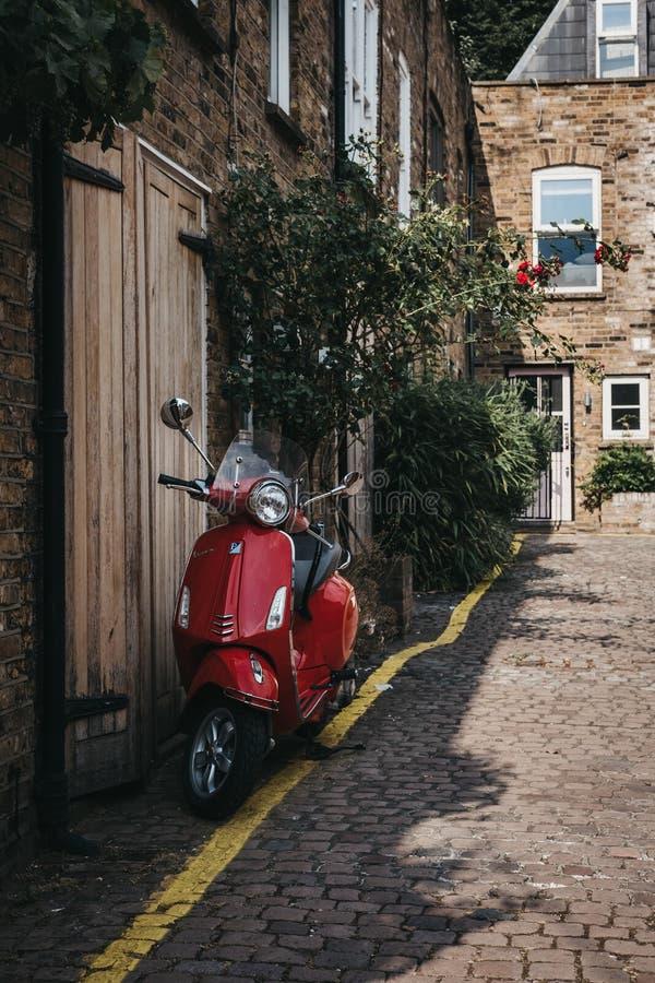 La moto roja del Vespa parqueada por una casa en Dunworth maúlla, Notting imagenes de archivo