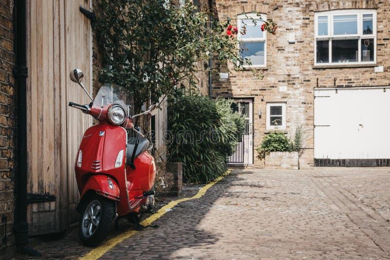 La moto roja del Vespa parqueada por una casa en Dunworth maúlla, Notting foto de archivo libre de regalías