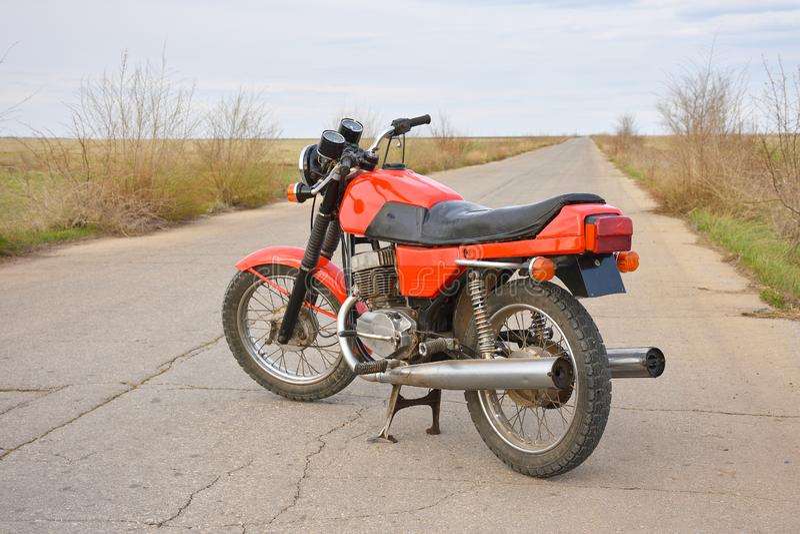 La moto rouge se tient sur la route vide image libre de droits