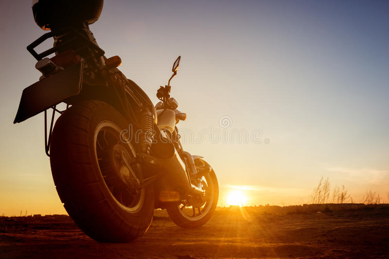 La motocicletta sta sulla strada del cielo del contesto del tramonto fotografia stock libera da diritti