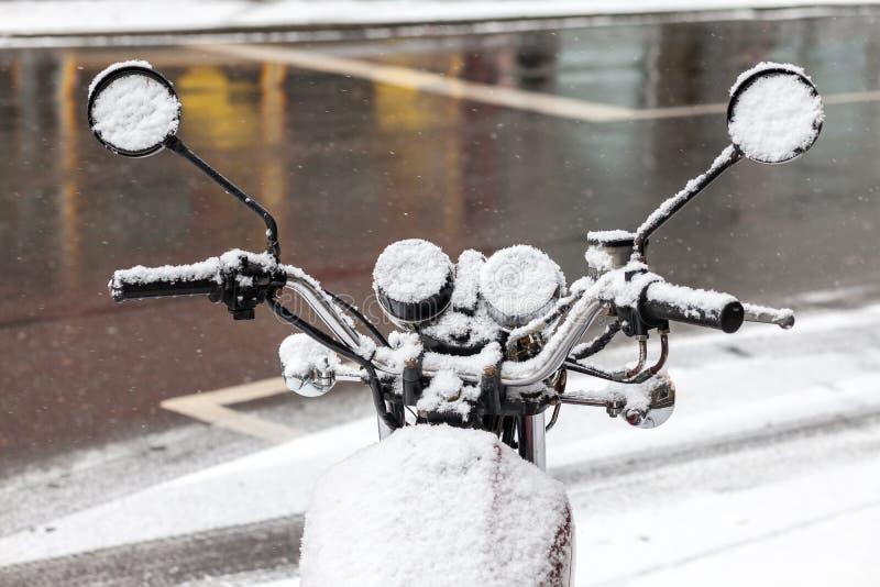 La motocyclette s'est garée sur la rue couverte de neige photo libre de droits