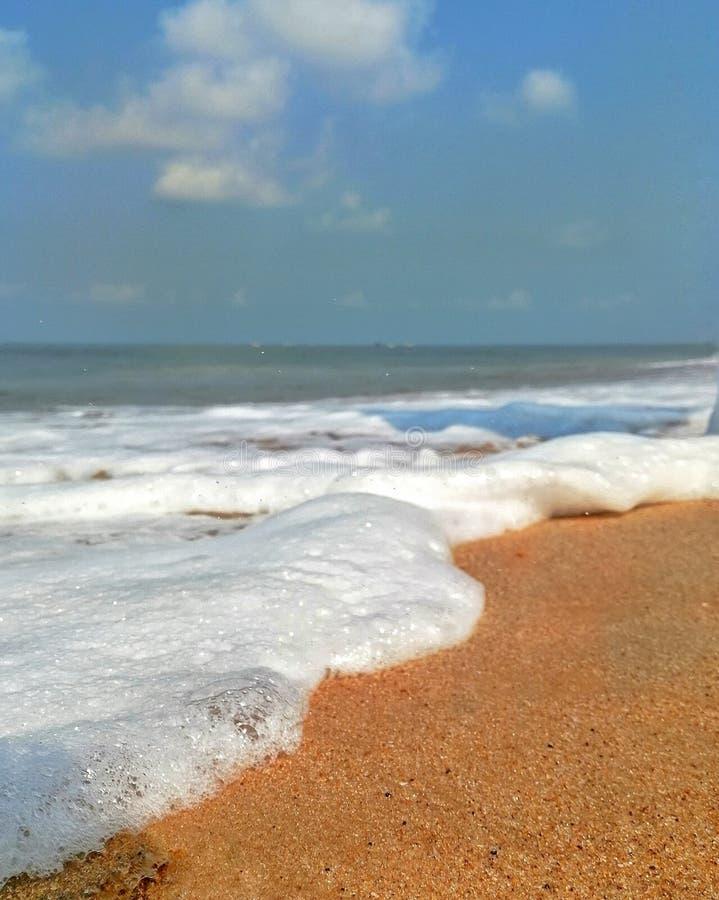 La mousse et les bulles lavées par les vagues douces à la plage de Goa Calungute photographie stock libre de droits