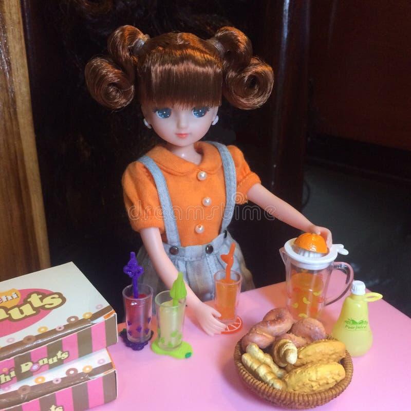 La muñeca adorable está haciendo el zumo de naranja imagen de archivo