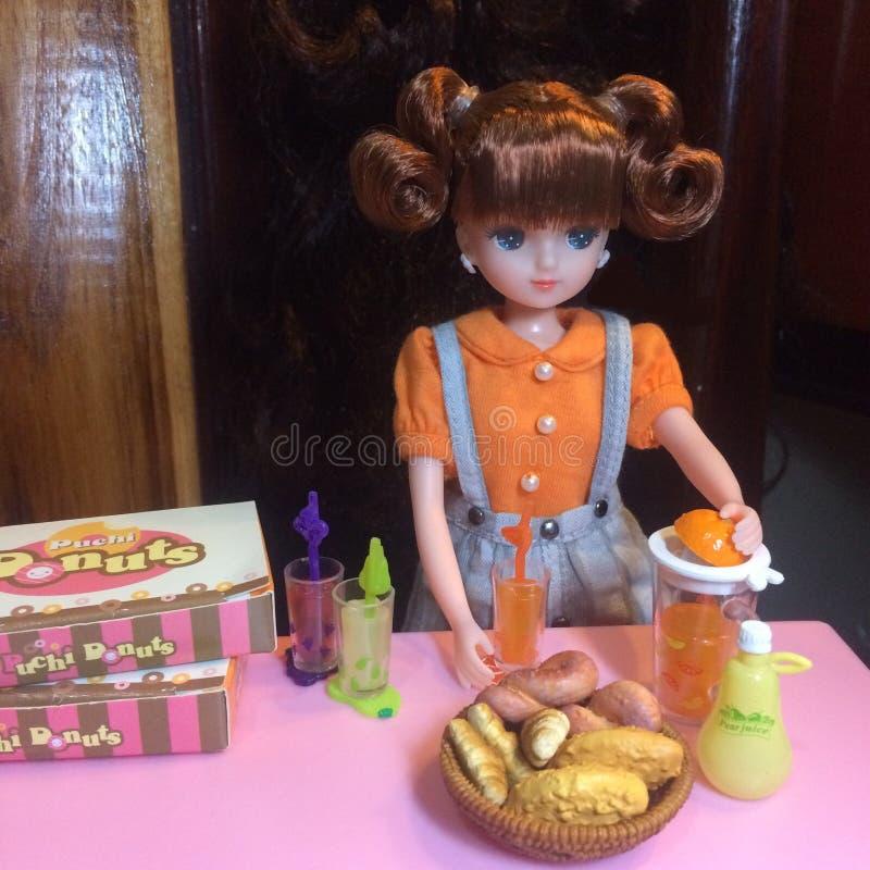 La muñeca adorable está haciendo el zumo de naranja fotografía de archivo libre de regalías