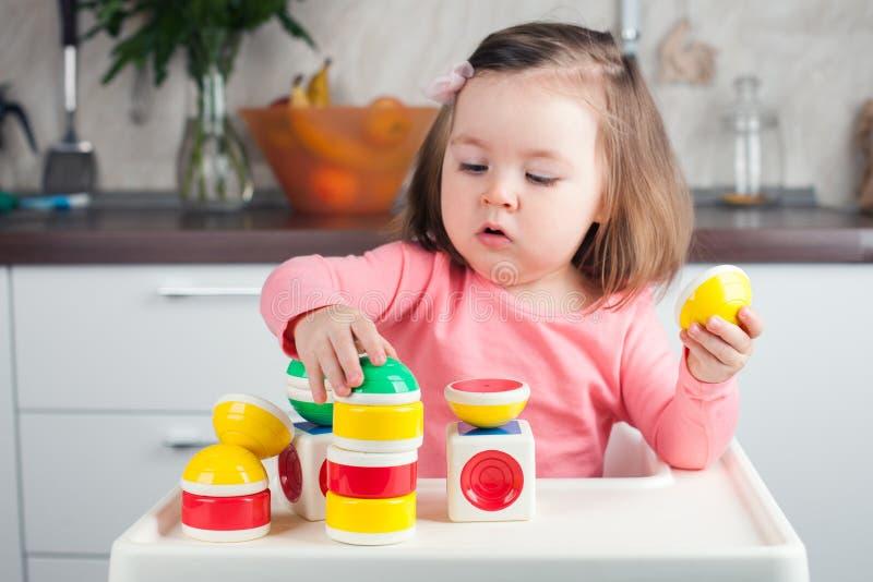 La muchacha 2 años con el pelo largo que jugaba con una construcción del diseñador en casa, construyendo torres, concentró el fun foto de archivo
