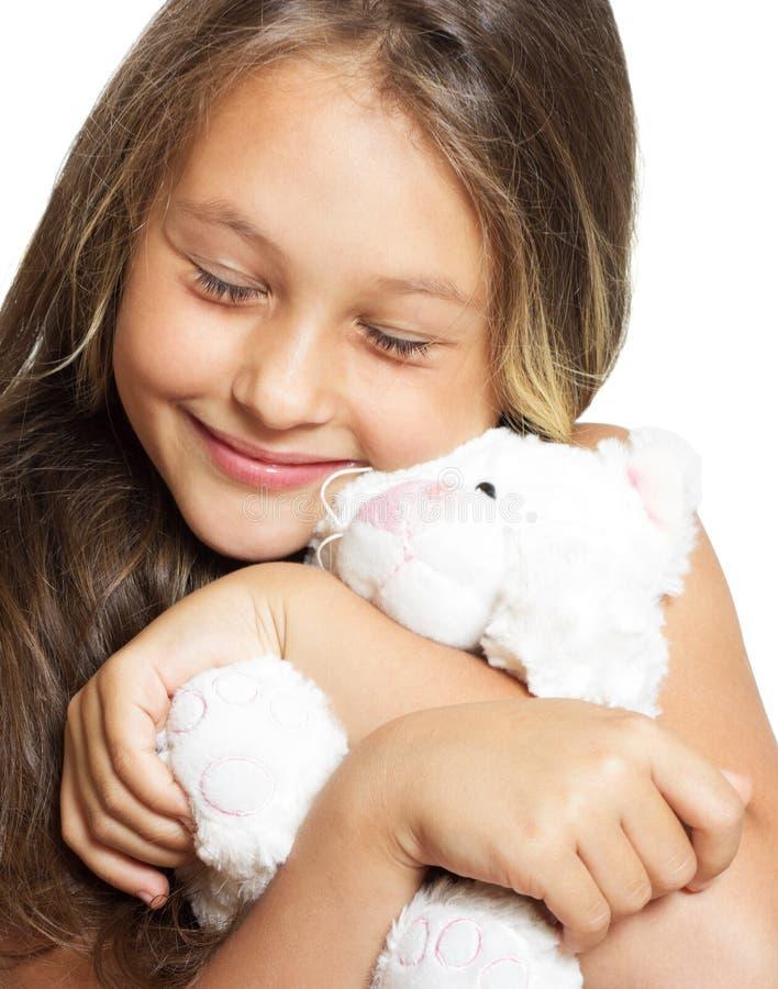 La muchacha abraza blando el juguete de la felpa imagen de archivo